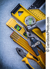 Set of construction tools on scratched metallic background