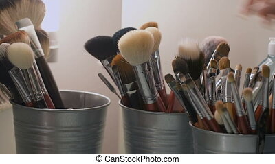 Set of cosmetic brushes. Makeup brushes in a bucket. stylist...