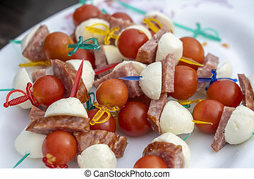 Set of delicious canapes , closeup. Many canapes with sausage, cheese and red tomato on a plate