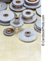 set of different gear cogwheel on brass metal background