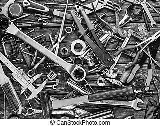 Set of different tools on wooden background, bw photo