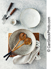 Set of dishes and kitchen utensils on a gray background, top view.