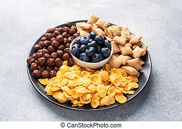 Set of dry cereal flakes for Breakfast with milk and berries. Healthy natural food. copy space Grey concrete background