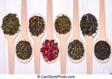 Set of dry herbal teas in wooden spoons on a white background. View from above.