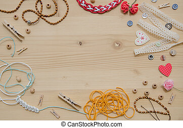 Elements for handicraft and decorative items for handmade like wooden beads, heart, buttons, decorative ribbons, braided bracelet ,rope, clips, wooden hearts, clothespins, buttons and thread. Flat lay