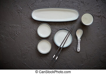 Set of empty ceramic dishes for sushi and rolls on a black...