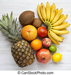 Set of fresh fruits on a white wooden table, top view. From above, overhead.