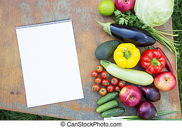 Set of fresh organic vegetables and fruits on rustic wooden table and notebook. Diet plan. Healthy food. Top view. From above.