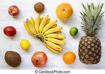 Set of fresh tropical fruits on a white wooden background, from above. Top view. Flat lay.