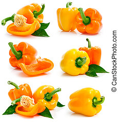 set of fresh yellow orange peppers with green leaves