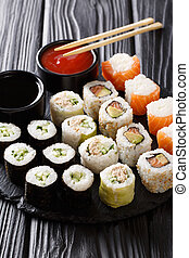 set of freshly prepared rolls with various fillings close-up with sauces on a board. vertical