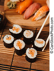 Set of fried sushi rolls with wasabi and ginger on a wooden background. Japanese oriental cuisine