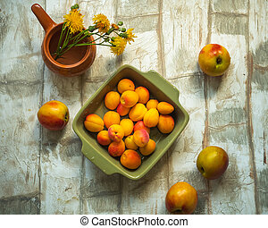 Set of fruit nectarine and apricot in a green square plate on a light table, shot from the top angle, a small vase with yellow flowers