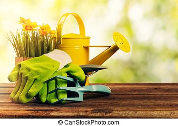 set of gardening tools on sunny bokeh garden background