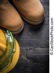 Set of goggles hard hat safety boots on wooden board