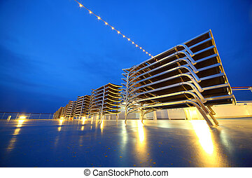 Set of illuminated deck-chair stack on ship deck in the evening