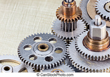 set of industrial cogwheels for machinery on brass background