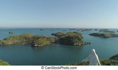 Set of islands in sea. Philippines. - Statue of Jesus Christ...