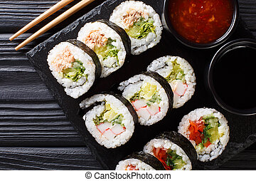 Set of japanese rolls futomaki with soy and chili sauces close-up on a slate board. horizontal top view