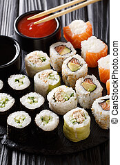 set of Japanese rolls in the assortment are served with sauces close-up on a stone. vertical