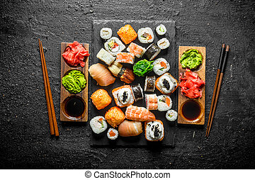 Set of Japanese sushi rolls for two with sauces and chopsticks.