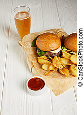 Set of junk food burgers and fries served with beer on white table