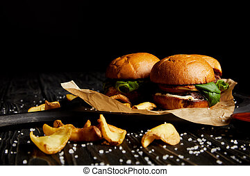 Set of junk food hamburgers and fried potatoes with scattered salt on wooden table