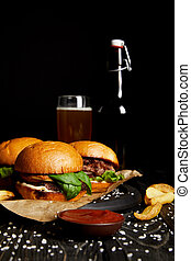 Set of junk food hamburgers on table with beer in bottle and glass