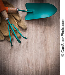 Set of leather working gloves gardening trowel and rake on wood