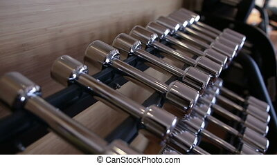 Set of metal dumbbell lying in a row on the stand...