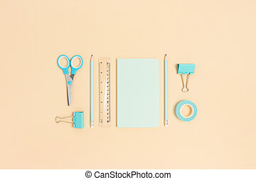 Set of mint color office supplies on a beige background.