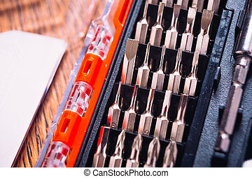 set of nozzles for screwdriver in red box on wooden background