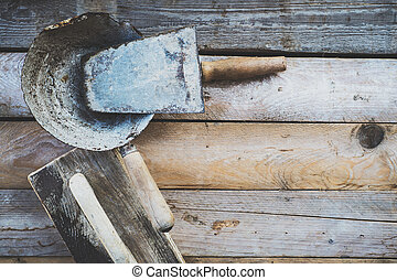 Set of old used masonry tools on a rough wooden surface