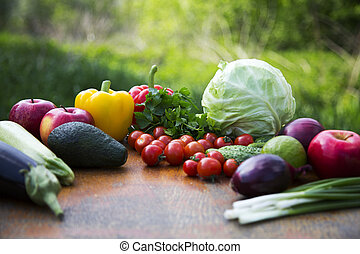 Set of organic vegetables and fruits on rustic wooden table and blur background. Side view.