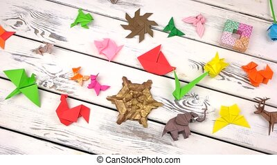 Set of origami objects on rustic wooden background....