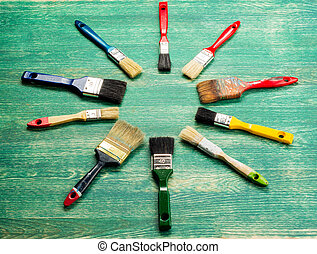 Set of paint brush on green wooden background. Top view.