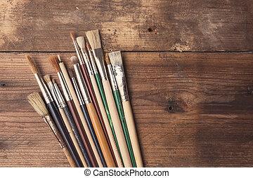 Set of paintbrushes on a wood background, tinted photo