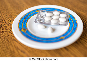 Set of pills in a plastic and foil package, on tray