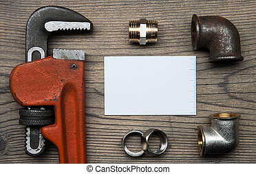 Set of pipes plumbing tools fittings and business card on the wooden background