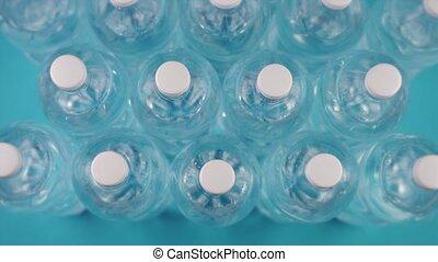 set of plastic bottles full of water on blue background