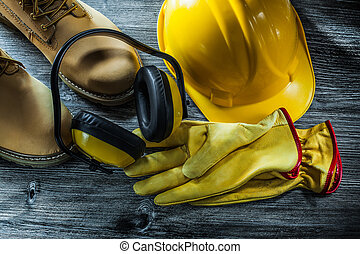 Set of protective workwear on wooden board.