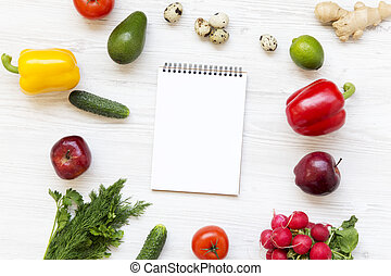 Set of raw food with notebook on white wooden background. Healthy food concept. Flat lay. Top view. From above.