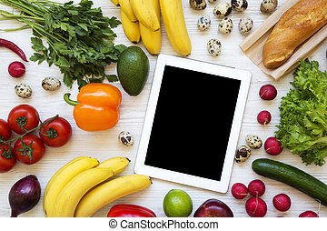 Set of raw food with tablet in the center on a white wooden background. Flat lay. Top view. From above.