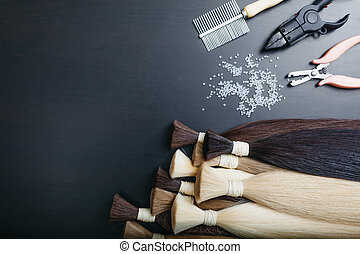 Set of sevral color hair extension tools on a dark...