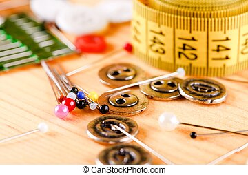 Horizontal photo with several sewing accessories as buttons, measuring tape, threads or pins. Detail is on several pins with nice color heads. Items are placed on light wooden board.