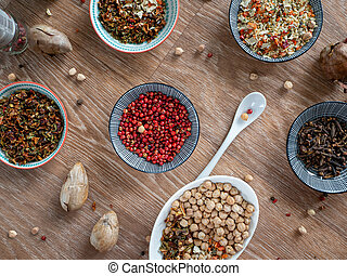 Set of spices and spices, chickpeas and other grains in small plates on a wooden table. Background with food ingredients that enhance the taste.