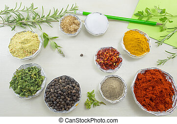Set of spices in shiny bowls with pen and paper for writing recipes on a white wooden table