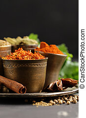 set of spices saffron, cardamom and paprika in a metal bowl