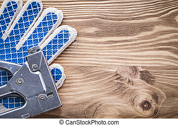 Set of staple gun protective gloves on wooden board