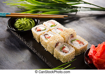 Set of sushi rolls with wasabi and ginger on black background. Japanese oriental cuisine